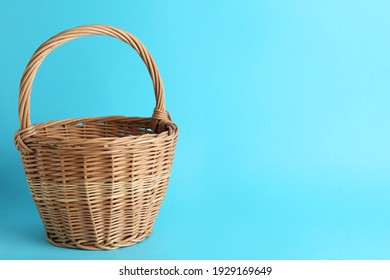 Empty wicker basket on light blue background, space for text. Easter item