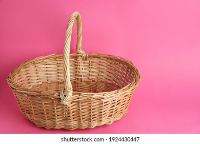 Empty wicker basket on pink background, space for text. Easter item