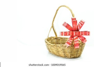 Empty wicker basket with red and gold ribbon isolated on white background