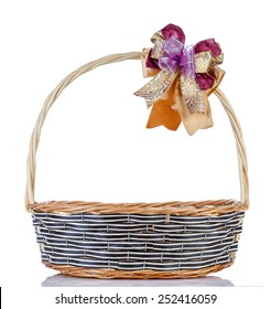 Empty wicker basket with ribbon on white background