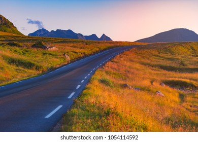 Empty winding country road in Norway, Europe, Scandinavia. Auto travel on sunset. Blue sky with clouds.