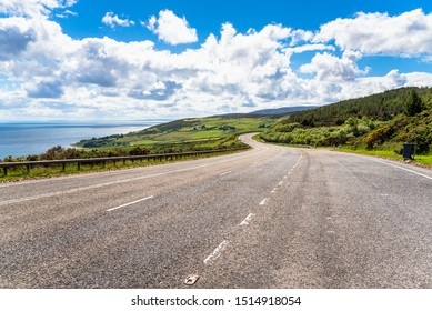 Empty winding highway along the coast on a clear spring day. Scotland, UK.
