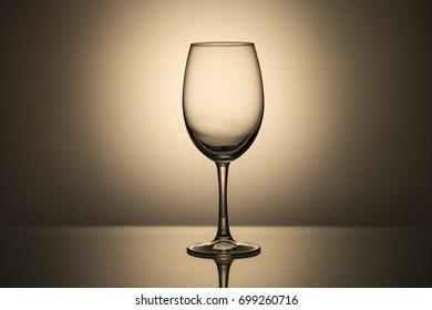 Empty wine glass on a monochrome background, light spot