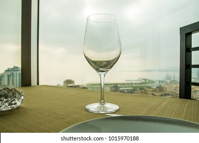 Empty wine glass on the table in front of a window