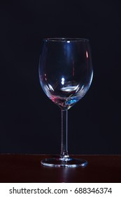 Empty Wine Glass in order on table over black background, low exposure