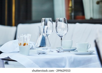 Empty wine glasses and coffee cup on the table of Parisian outdoor cafe