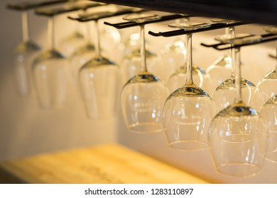 Empty wine glasses hanging on bar rack, photo with blurred background