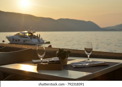 Empty wine glasses on a seashore restaurant table, with a reservation sign-and a boat on sea