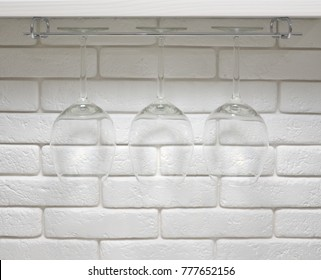 Empty wine glasses on a white brick wall background