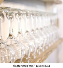 Empty wine glasses in row on wooden bar. Selective focus.