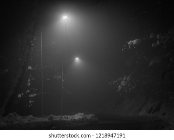 Empty winter asphalt road at night illuminated by dot lamps with roadside covered by snow in the  Misterious dark night.