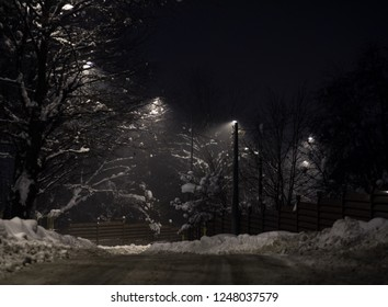 Empty winter asphalt road at night illuminated by dot lamps with roadside covered by snow and fence in the  Misterious dark night.