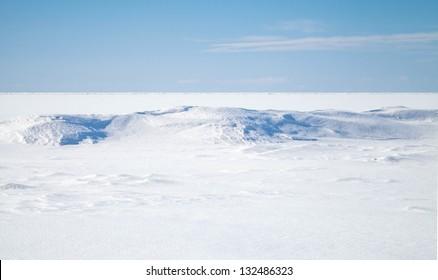 Empty winter background landscape. Blue sky, snow on frozen Baltic Sea