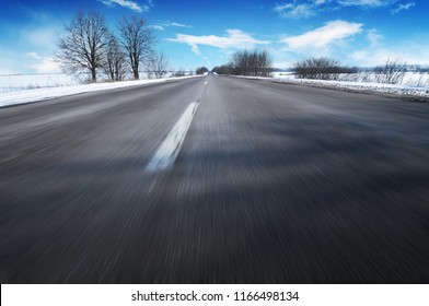 Empty winter countryside road in motion with trees and white snow against blue sky with clouds
