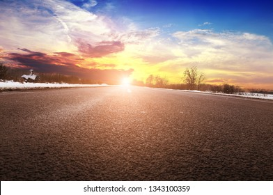 Empty winter countryside road with trees and white snow against night sky with sunset