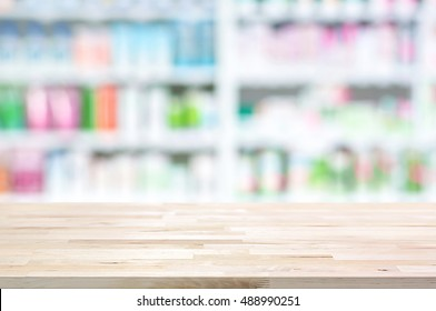 Empty wood counter top on blur pharmacy shelf (or chemist and cosmetic shop) background