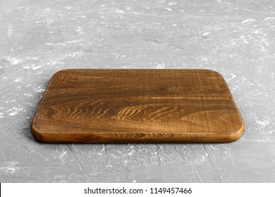 Empty wood cutting board on gray background with copy space. Perspective view.