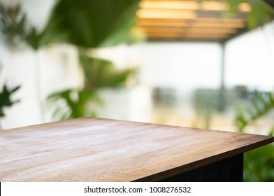 empty wood desk over blurred montage coffee shop cafe / restaurant background