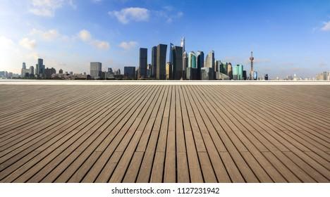 Empty wood floor with city landmark buildings background at Shanghai bund panorama Skyline