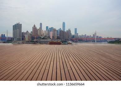 Empty wood floor with city landmark buildings background at Chongqing Skyline