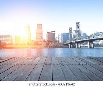 empty wood floor near steel bridge over water with cityscape and skyline of portland at sunrise
