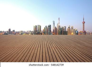 Empty wood floor surface with modern city landmark buildings of Shanghai bund Skyline of morning