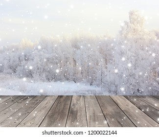 Empty wood flooring on blurred winter background. Empty space for Your object. Backdrop, table layout with winter landscape and snowflakes.