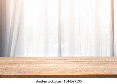 Empty of wood table with Blur of curtain window and pillow in livingroom with sunlight. For montage product display or design key visual layout.