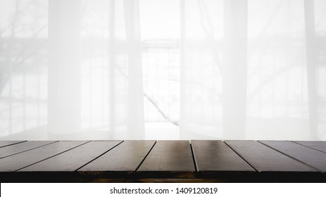 Empty of wood table with Blur curtain window and stationery box with sunlight. Using for Mock up template for craft display of your design,Banner for advertise of product.