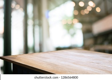 empty wood table with blur montage restaurant background.