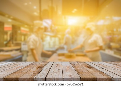 Empty wood table with blur open cooking restaurant background,chefs cooks in the kitchen customer can see they are cook at food counter,Mock up Template for montage of your product ,vintage color