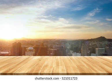Empty wood table and blurred Perspective sunset city view with twilight sky can be used for display or montage your products.