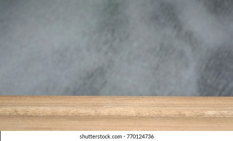 Empty wood table with blurred raw concrete (Beton brut) , use for montage to display the products or foods. Selective focus.