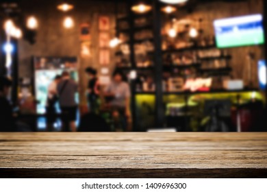 Empty wood table and blurry background of bar cafe for product display montage.