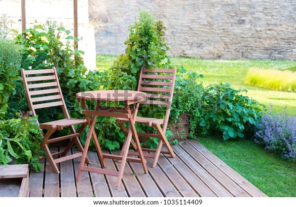 Tisch und Stühle aus hellem Holz auf der Terrasse im Sommer