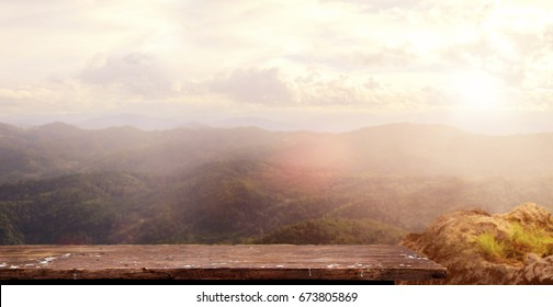 Empty wood table and  the mountains that glow under sunlight ,dramatic morning scene. For product display montage.