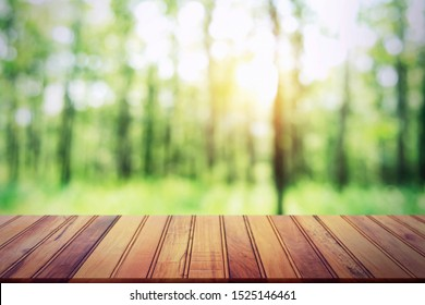 empty wood table on blur forest background for design product