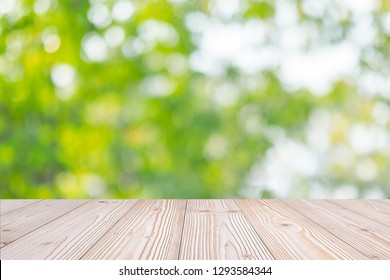 Empty wood table on green natural background in the garden outdoor. Mock up for your product display or montage