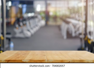 Empty wood table space platform and fitness gym background. Product display montage Concept.