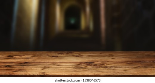 Empty wood table surface in front of gloomy vault with short depth of field for a halloween background