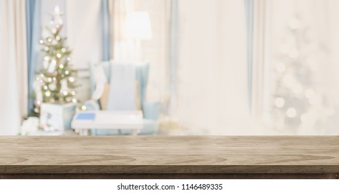 Empty wood table top with abstract warm living room decor with christmas tree blur background with bokeh light,Holiday backdrop,Mock up banner for display of advertise product ,luxury house