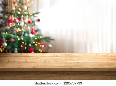 empty wood table top and blur of room with a christmas tree background, suitable for montage product display.