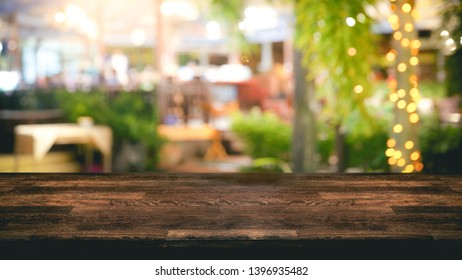 Empty wood table top and Blur light reflection green palm leaves or tree in tropical forest at restaurant, pub or bar at night. Blurred background for product display.
