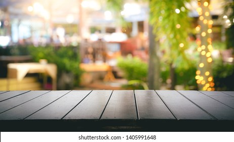 Empty wood table top and Blur light reflection green palm leaves or tree in tropical forest at restaurant, pub or bar at night. Blurred background for product display  with several concept.