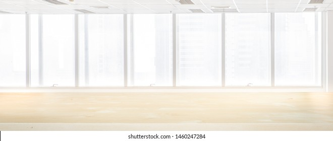 Empty wood table top with Blur inside office building with window background, interior and business background. Using for Mock up template for craft display of your design.