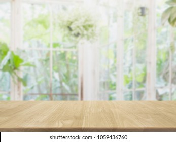 Empty wood table top and blurred of interior room with window view green from tree garden background background - can used for display or montage your products.