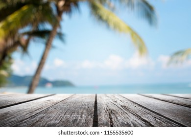 Empty wood table top and blurred Palm tree summer beach with blue sea and sky background. - can used for display or montage your products.