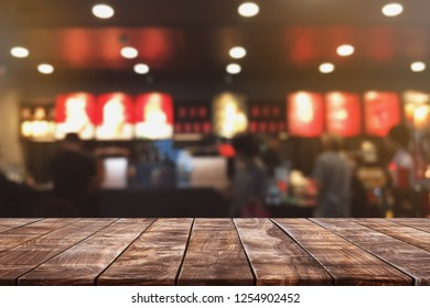 Empty wood table top and blurred bokeh cafe and coffee shop interior background with vintage filter - can used for display or montage your products.