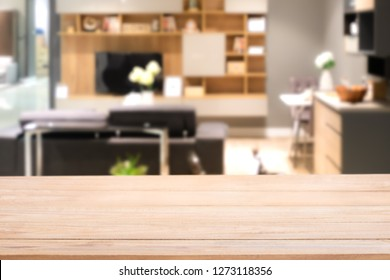 Empty wood table top with Blurred abstract mock up of modern living room interior with elegant black leather sofa. Decorated with shelf, TV and dining table. Can be used for background.
