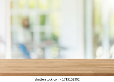 Empty wood table top and blurred of interior restaurant with window view green from tree garden background background - can used for display or montage your products.